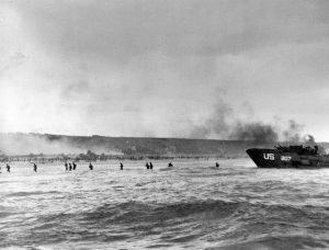 Under the cover of naval shell fire, American infantrymen wade ashore from their landing craft during the initial Normandy landing operations in France, June 6, 1944. (AP Photo/Peter Carroll)