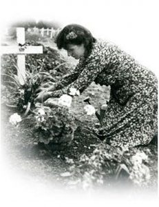 French Normand lady putting flowers on a grave